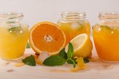 Orange fruktsaft och lemonad med mintkaramellen i krus Royaltyfri Bild