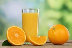 Orange fruktsaft och nya apelsiner i sommar Royaltyfri Bild
