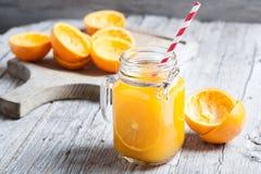Orange fruktsaft på exponeringsglas på den lantliga trätabellen Arkivfoto