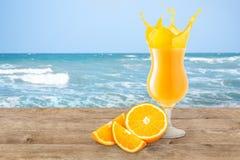 Orange fruktsaft på strandtabellen Royaltyfri Fotografi