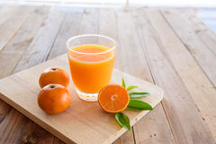 Orange fruktsaft på träbakgrund Arkivfoton