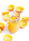 Orange fruktsaft på vit bakgrund med sammanpressade skal Royaltyfria Bilder
