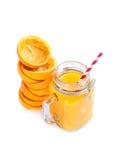 Orange fruktsaft på vit bakgrund med sammanpressade skal Arkivbild