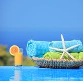 Orange fruktsaft, sjöstjärna och handdukar bredvid en pöl royaltyfria foton