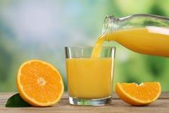 Orange fruktsaft som häller in i ett exponeringsglas i sommar Royaltyfri Foto