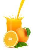 Orange fruktsaft som häller in i ett exponeringsglas med färgstänk. Royaltyfri Fotografi