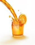 Orange fruktsaft som häller in i plaska för exponeringsglas. royaltyfri fotografi