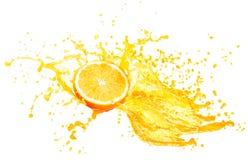 Orange fruktsaft som plaskar med dess frukter på vit royaltyfri bild