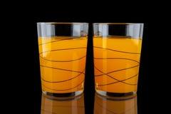 Orange fruktsaft - två exponeringsglas med apelsiner på svart bakgrund Arkivfoton
