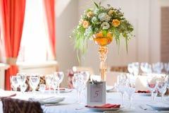 Orange fuchsia flower arrangement wedding decoration. In restaurant Royalty Free Stock Photos