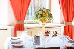 Orange fuchsia flower arrangement wedding decoration. In restaurant Royalty Free Stock Images