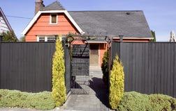Orange gammalt hus med det höga staket Royaltyfri Bild