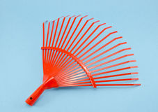 Orange garden rake on azure background Royalty Free Stock Image