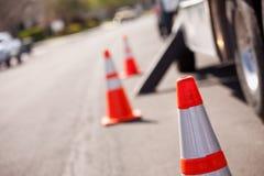 Orange Gefahr-Kegel und Dienst-LKW in der Straße Stockfotografie