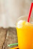 Orange gefrorenes Slushie in der Plastikschale mit Stroh Stockbilder