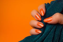 Orange gefunkelte Nagelmaniküre Lizenzfreie Stockfotografie