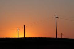 Orange, gelber Sonnenuntergang und elektrische Masten Stockfotografie
