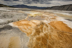 Orange geothermal pools, mountains and dark clouds, Yellowstone Stock Photo