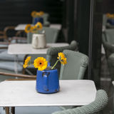 Orange gerbera in blue kettle with rust as a table decoration in a cafe Stock Photos