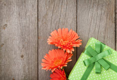 Orange gerbera flowers and gift box Royalty Free Stock Images