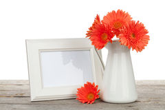 Orange gerbera flowers and photo frame on wooden table Royalty Free Stock Photography
