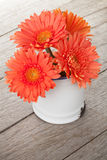 Orange gerbera flowers in pitcher Royalty Free Stock Images