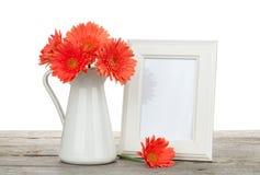 Orange Gerberablumen und Fotorahmen auf Holztisch Stockbild