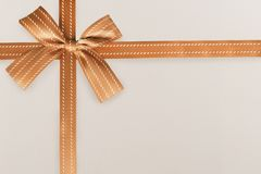 Orange gift ribbon and knot on a white textured pattern in background. stock photo