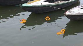 Orange girlander av rituella blommor i den sakrala Ganga floden arkivfilmer