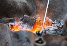 Orange glödande kol som täckas med askaslut upp Arkivbild