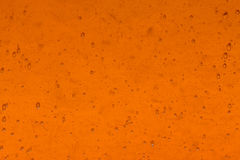 Orange glass background. Orange color glass with air bubbles background Stock Photo