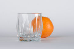 Orange with glass. Orange behind empty glass on the white background Stock Images