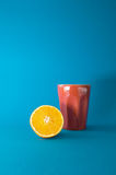 Orange and a glass on blue background Royalty Free Stock Photos