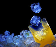 Orange glass and ice. In blue light Royalty Free Stock Photography