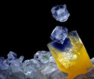 Orange glass and ice. In blue light Royalty Free Stock Photo