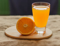 Orange and glass of juice. Half a glass of orange juice on the cutting board dark background Stock Images
