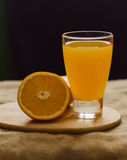 Orange and glass of juice vertical view. Half a glass of orange juice on the cutting board dark background Royalty Free Stock Images