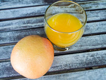 Orange and Glass of Orange Juice. Orange and glass of juice on the wooden table Stock Photos