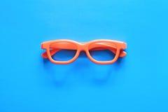 Orange glasses on a blue background stock photo