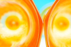 Orange glassy abstract background. Two orange glass forming abstract pattern on blue background with one part defocused stock photos