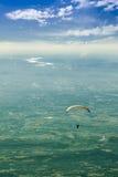 Orange glidflygplan som förbiser Rhonen under en molnig himmel Arkivbild