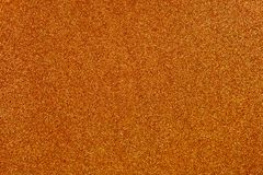 Orange Glitter Background. Burnt orange colored sand paper textured background with sparkles and glitters stock photos