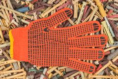 Orange gloves lying on the background of the dowels. Stock Images