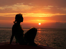 The Orange Glow. Silhouette of a woman with an orange glow gazing at the sunset Royalty Free Stock Photos