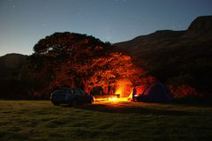 The orange glow of a brightly burning camp fire at night Stock Photos