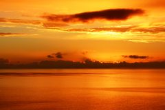 Orange glow over calm sea at sunset. View of a sunset over the Firth of Forth in Scotland seen from the road overlooking the Firth of Forth near Dunure in South Royalty Free Stock Images