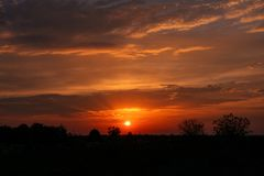 Orange glow sky sunset in the field Royalty Free Stock Image