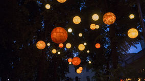 Orange glowing orbs float in night sky. Orange orbs of various shades float below some trees lighting up the area in a fun exciting mood stock image