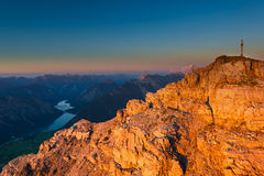 Orange glowing rocks of mountain peak with cross Stock Photography