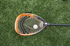 Orange goalie stick with a ball. Orange and black lacrosse goalie stick with a ball in the net lying on a green turf field stock photo